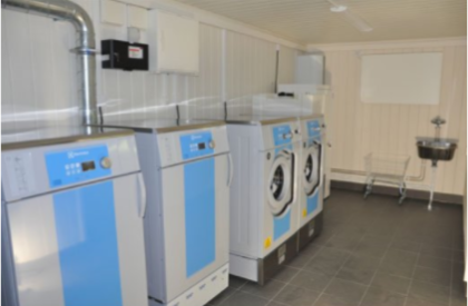 Multiple washers placed in a row in a laundry house module